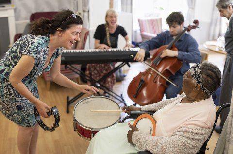 A group of people with dementia playing musical instruments, assisted by a Music in Mind therapist.